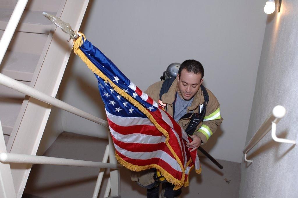 In honor of 9-11, the flag is carried up the high-rise stairs.