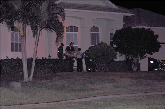 The stabbing victim is brought out of a Marco house by emergency personnel.