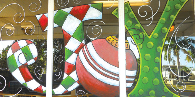 Denise Santos of Goodland painted the post office window to help the village get into the holiday spirit. Photo by Joanie Fuller