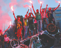 People light flares as they stand on top of an overturned car. SUBMITTED PHOTOS