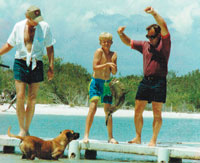 Brian helps a friend's son pull up a triple tail from the dock. Jake the dog looks on with excitement.