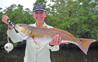 Jill holding a nice 30 inch back water red for a quick photo before releasing it.
