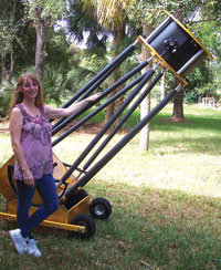 """The 20"""" home-made telescope with the wheels still attached. Model is Jackie Richards of the Everglades Astronomical Society. PHOTO BY MIKE P. USHER"""
