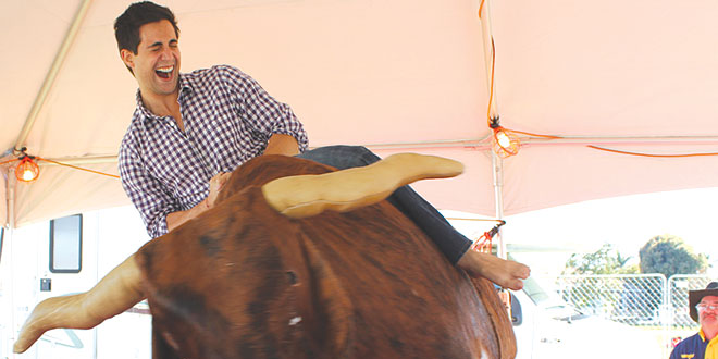 Nick Ciletti, morning news anchor of NBC-2 News, rides the mechanical bull.
