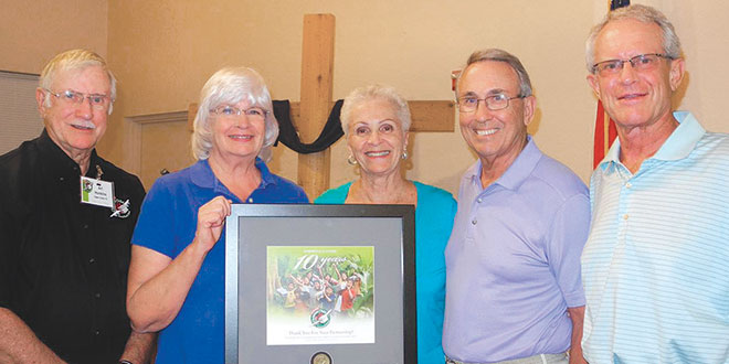Operation Christmas Child Area Coordinators for Southwest Florida Art and Bonnie Hunkins, left, present a ten-year service plaque to Marco Presbyterian Church members Lois and Jerry Oxborough and Jim Stifler at the conference.