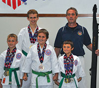 Posing for a picture with their sensei, the students with the medals they earned at the 2014 AAU Junior Olympics.