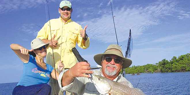 Walter Donavan holds a nice Redfish as Danielle and Jasen bust a move.