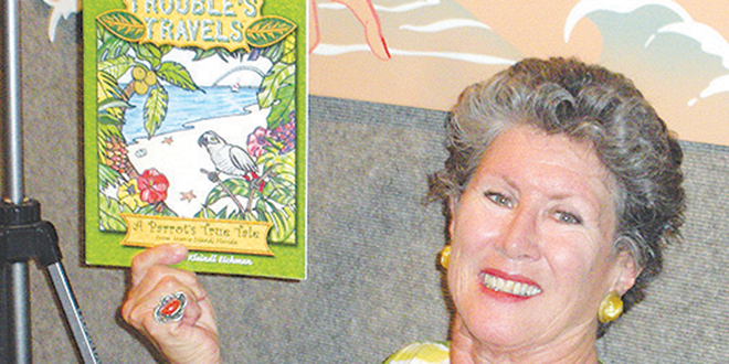 "Kathleen Eichman and her coloring book entitled ""Trouble's Travels,"" based on the escapades of ""Trouble,"" the African Gray Parrot perched over her shoulder."