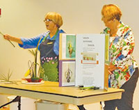 Connie Lowery, left, and Sue Oldershaw demonstrate use of plant materials to create a pleasing design.