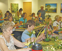 Calusa Garden Club members walk around the room to provide tips and encouragement to workshop participants.