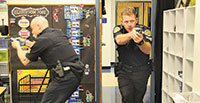 The officers entering and searching the room in pairs. PHOTOS BY SAMANTHA HUSTED