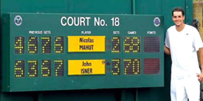 Isner standing next to the Wimbledon scoreboard showing his longest  match in tennis history score. SUBMITTED PHOTOS