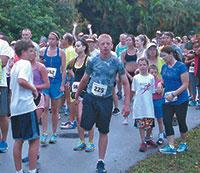 Runner #225, Tanner Harvey warms up before running the 5k