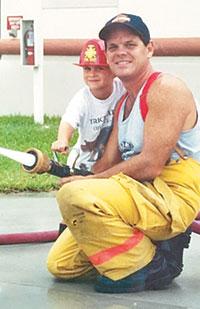 Chris shows son Joseph how the fire hose works.