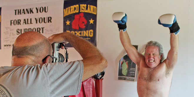 Robert Eder takes a photo of Jimmy Downey. Jimmy's image will occupy the second half of the mural.