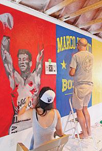 Stephanie Simon and Robert Eder work onthe mural.