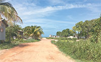 Paved only six years ago, Placencia's main road used to look like this red dirt road.