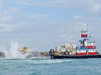 Above water, materials being dropped into the Gulf to create the artificial reef.